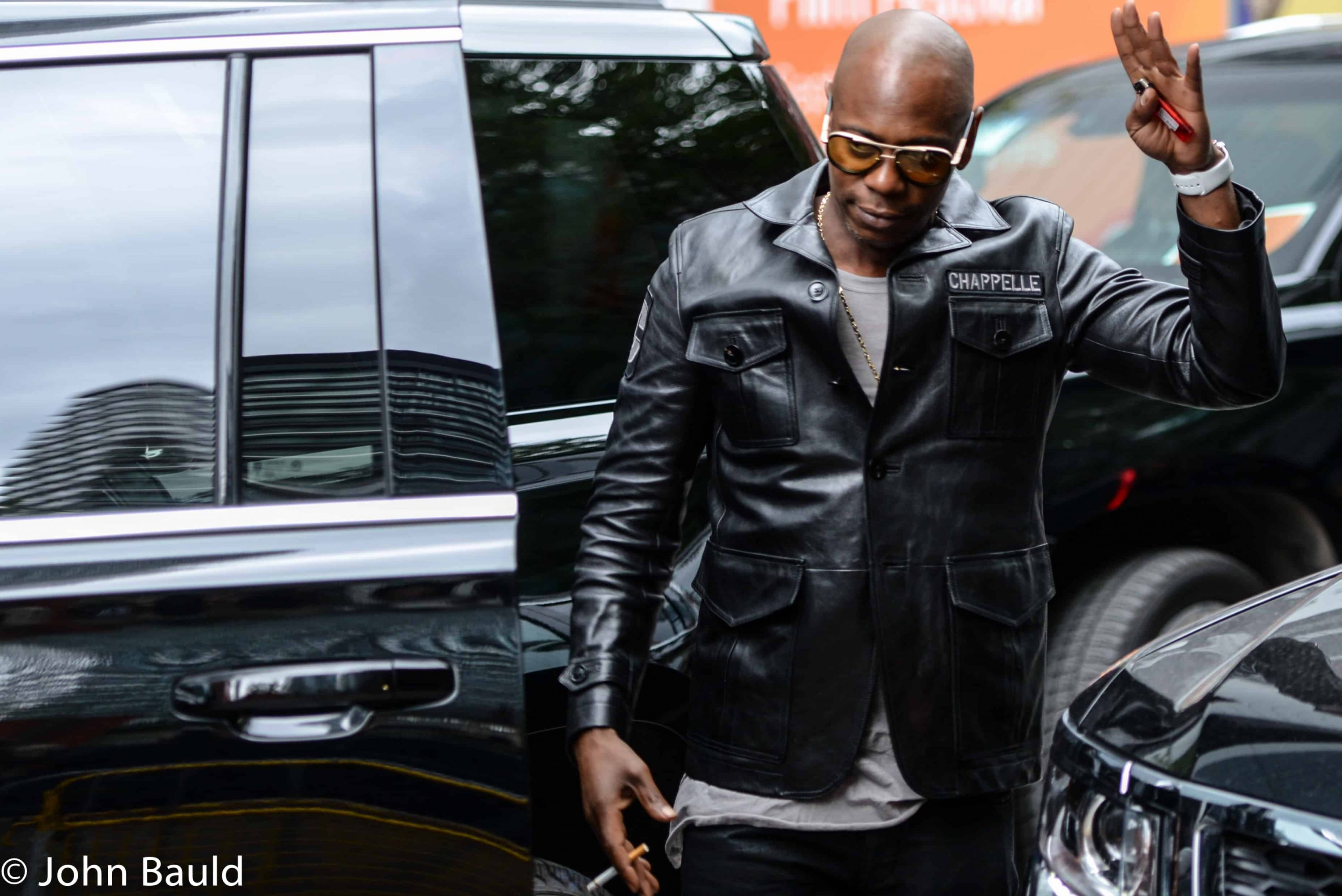 Dave Chapelle in leather jacket coming out of his car