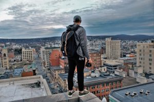 young hipster standing on the edge of a high rise building