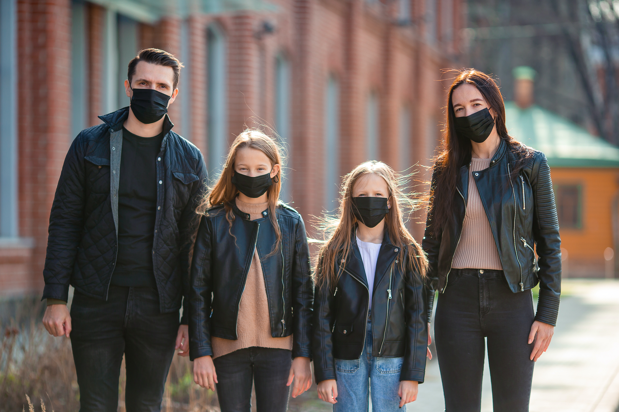 A family is seen wearing black masks to protect themselves against Coronavirus